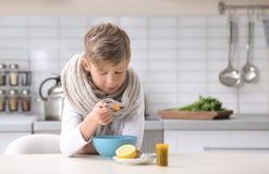 吃汤的病的小男孩治疗寒冷在桌上 库存照片