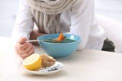 吃汤的病的小男孩治疗寒冷在桌上 免版税库存图片