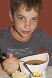 吃汤的逗人喜爱的十几岁的男孩 库存照片