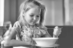 吃汤的逗人喜爱的小女孩在餐馆 免版税图库摄影