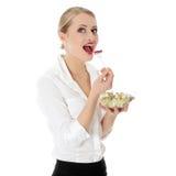 吃沙拉年轻人的女实业家 免版税库存图片