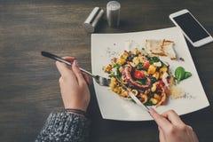 吃沙拉用章鱼和菜pov 免版税库存图片