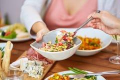 吃沙拉的人们在桌上用食物 免版税图库摄影