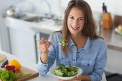吃沙拉的俏丽的妇女 免版税库存照片
