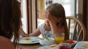 吃沙拉的女孩坐在咖啡馆在城市 吃午餐的逗人喜爱的青少年的女孩在咖啡馆 股票视频