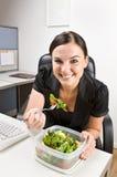 吃沙拉的女实业家服务台 免版税图库摄影