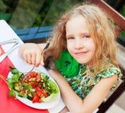 吃沙拉的孩子在咖啡馆 免版税库存图片