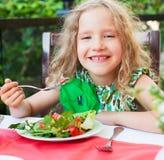 吃沙拉的孩子在咖啡馆 免版税图库摄影
