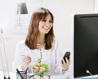 吃沙拉的少妇创造性的设计师,当工作在办公室时。 库存图片