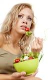 吃沙拉的微笑的妇女 图库摄影