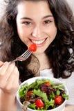 吃沙拉的愉快的女孩 免版税库存照片