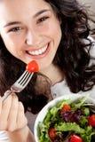 吃沙拉的愉快的妇女 免版税库存照片