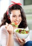 吃沙拉的新美丽的妇女 免版税库存图片