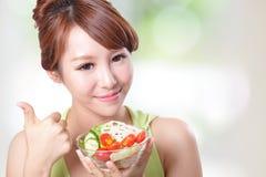 吃沙拉的有吸引力的妇女微笑 免版税库存图片