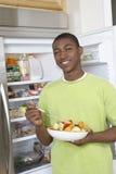 吃沙拉的男孩由开放冰箱 免版税库存图片