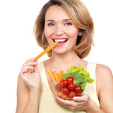 吃沙拉的美丽的年轻健康妇女 免版税库存照片