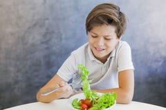 吃沙拉的青少年的男孩不快乐 免版税库存照片