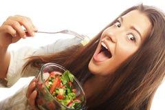 吃沙拉的年轻愉快的妇女。 免版税库存图片