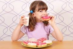 吃油炸圈饼和饮料牛奶的小女孩 库存图片