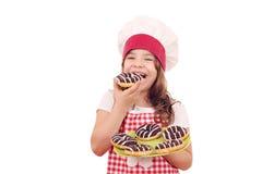 吃油炸圈饼的饥饿的小女孩厨师 免版税库存图片