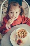 吃油炸物和蕃茄-顶视图的逗人喜爱的微笑的女孩 库存照片