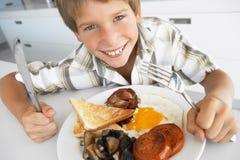 吃油煎的不健康的年轻人的男孩早餐 库存图片