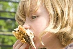 吃油煎的女孩的鸡 免版税库存图片