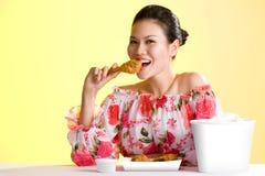 吃油煎的妇女年轻人的鸡 库存图片