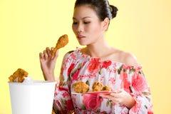 吃油煎的妇女年轻人的鸡 图库摄影