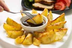 吃油煎的楔子土豆 免版税库存照片