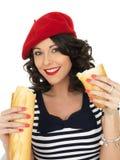 吃法国棍子面包大面包的可爱的少妇 免版税库存照片