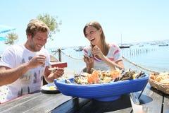吃海鲜的Coouple在餐馆 免版税库存照片