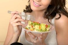 吃混杂的叶子沙拉的健康妇女 免版税库存照片