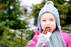 吃温暖的奶蛋烘饼的可爱的小女孩在冷的冬日 免版税库存图片