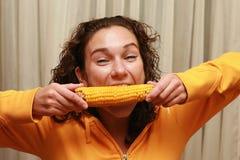 吃滑稽的女孩年轻人的玉米 免版税库存图片