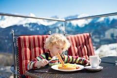 吃滑雪后的午餐的孩子 冬天孩子的雪乐趣 库存照片