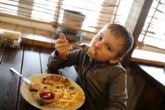 吃炸肉排的孩子 免版税库存照片