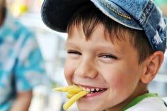 吃炸薯条的男孩 免版税库存图片
