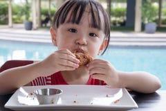 吃炸鸡的亚裔矮小的中国女孩 库存照片