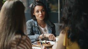 吃点心和喝在咖啡馆的年轻女人咖啡谈话获得乐趣 股票录像