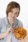 吃烤干酪辣味玉米片的美丽的妇女 库存照片