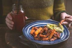 吃烤红萝卜用鲕梨调味汁的妇女 库存照片