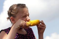 吃煮沸的玉米的女孩 免版税库存照片