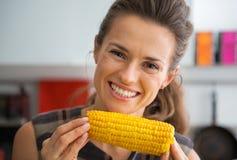吃煮沸的玉米的少妇在厨房里 免版税库存照片