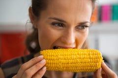 吃煮沸的玉米的少妇 库存照片