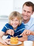 吃父亲他微笑的儿子奶蛋烘饼 免版税图库摄影
