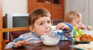 吃牛奶店早餐的两个愉快的孩子 库存照片