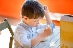 吃牛奶店早餐的逗人喜爱的小男孩 免版税图库摄影
