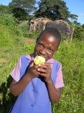 吃狂放的果子的非洲schoolkid 库存图片