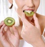 吃猕猴桃的健康妇女 库存图片